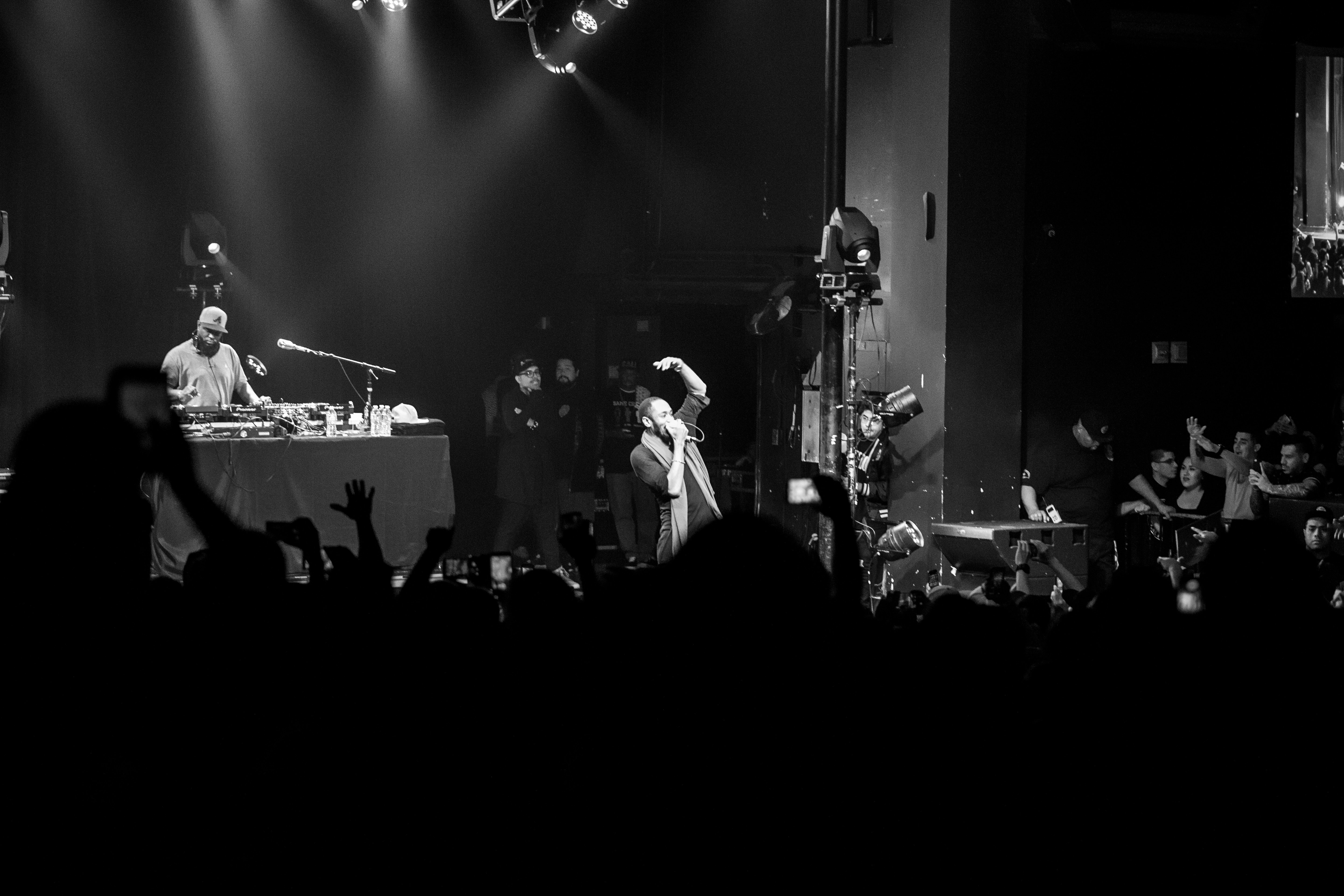 grayscale photo of a concert on the stage