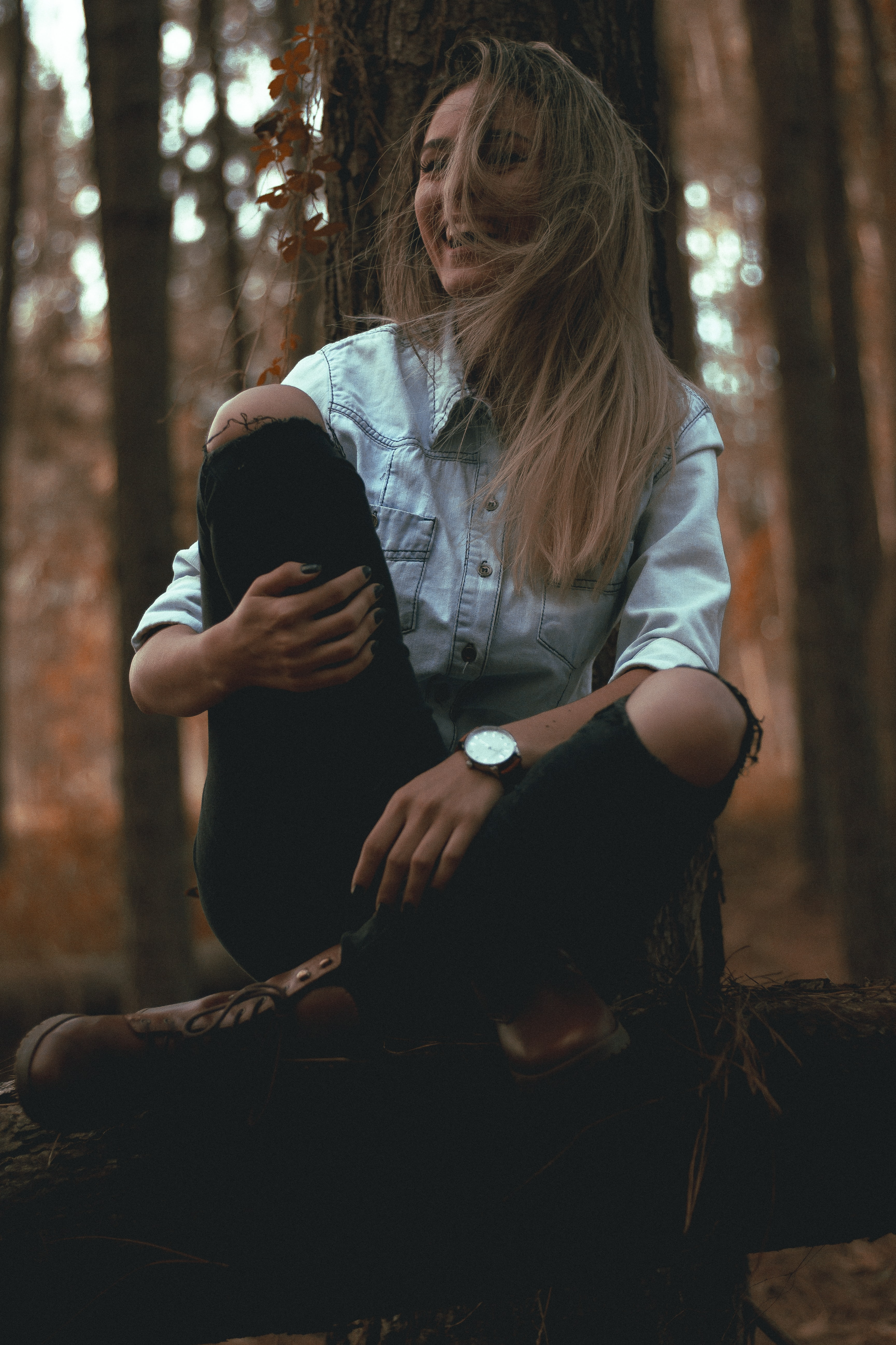 laughing woman leaning on gray tree trunk