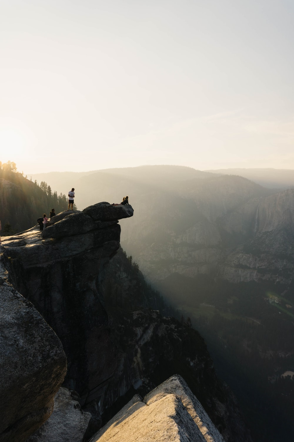 people standing on cliff with clear blue sky during daytime