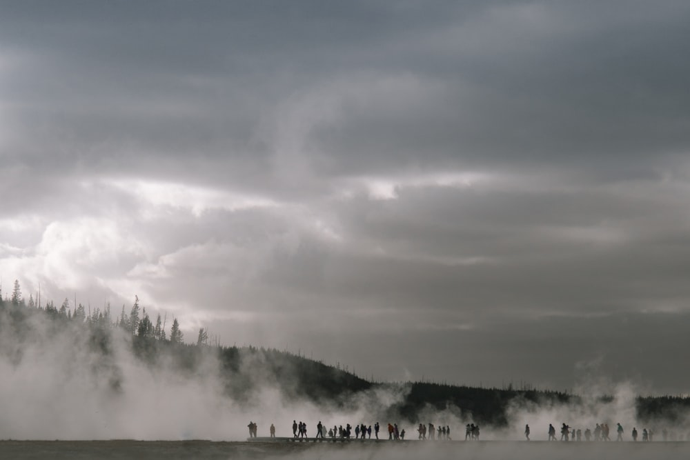 people near mountain with fogs
