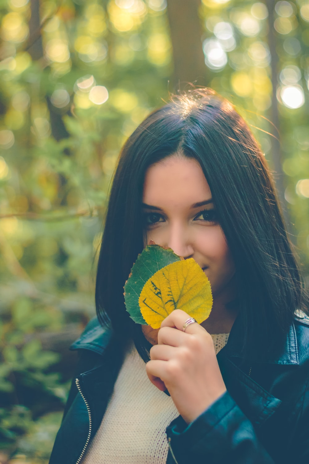 woman holding yellow and green leaves