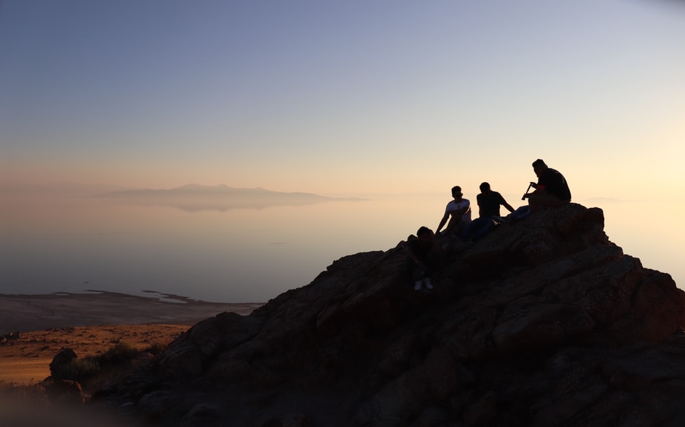 silhouette of men sitting on hill at daytime
