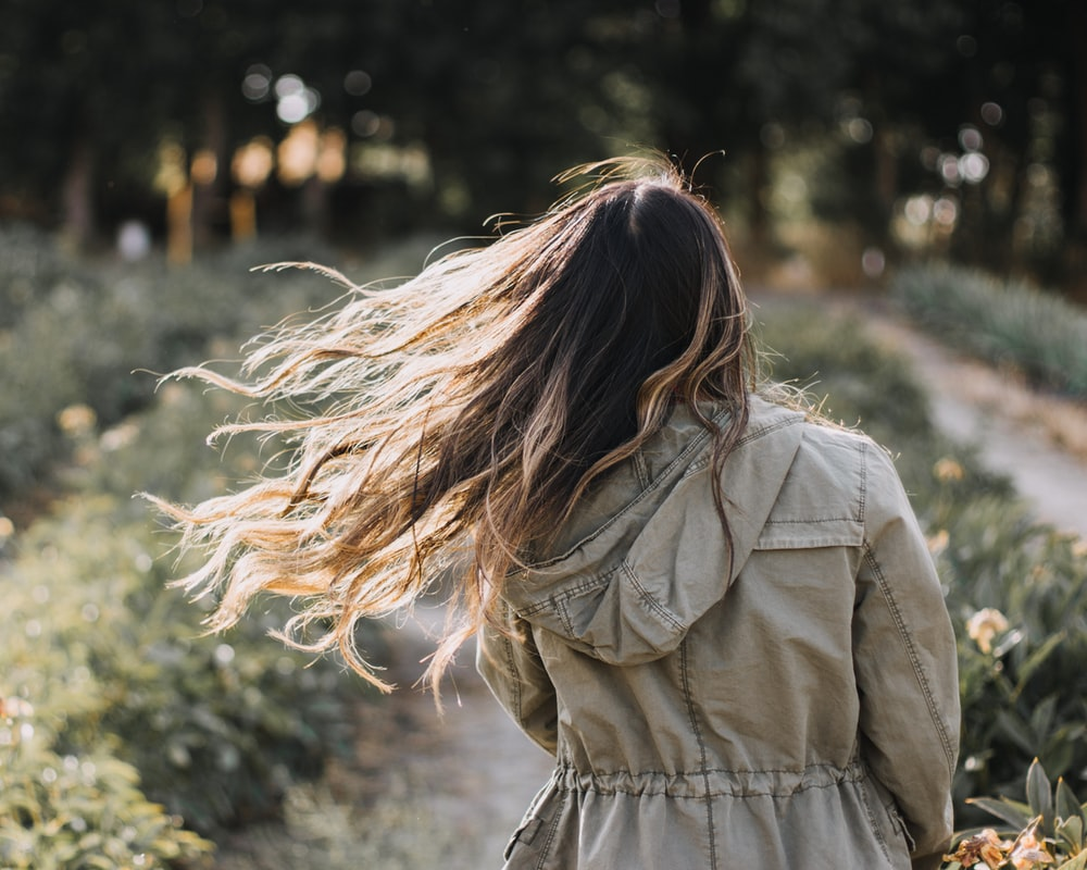selective focus photography of woman standing surrounded by plants