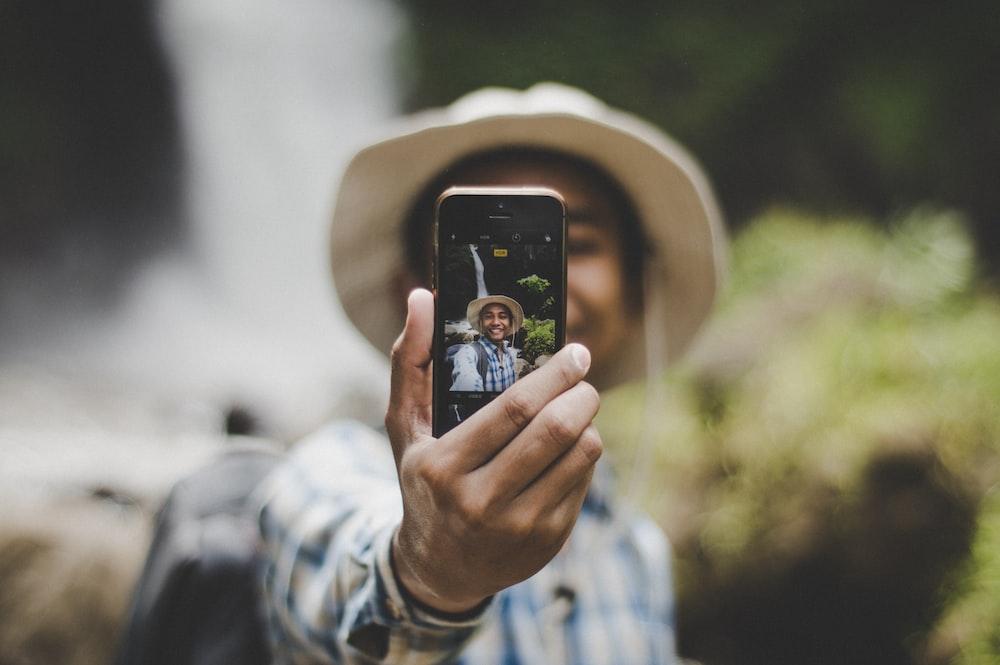 man wearing brown hat taking selfie