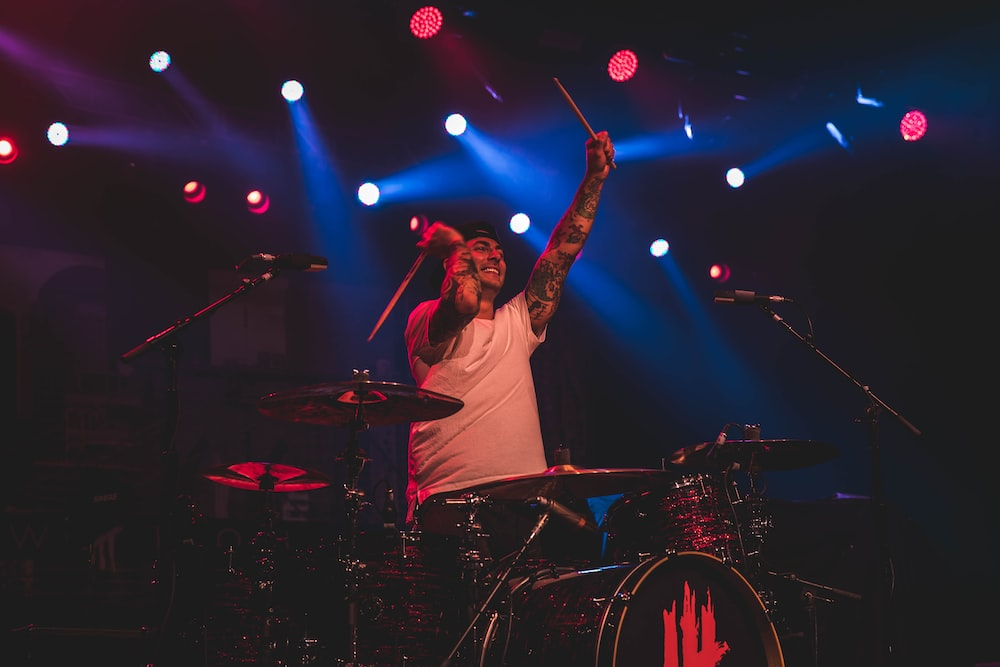 man playing drums with spotlights