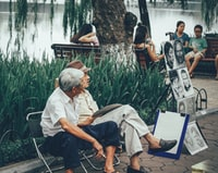 two men sitting on bench beside portrait paintings
