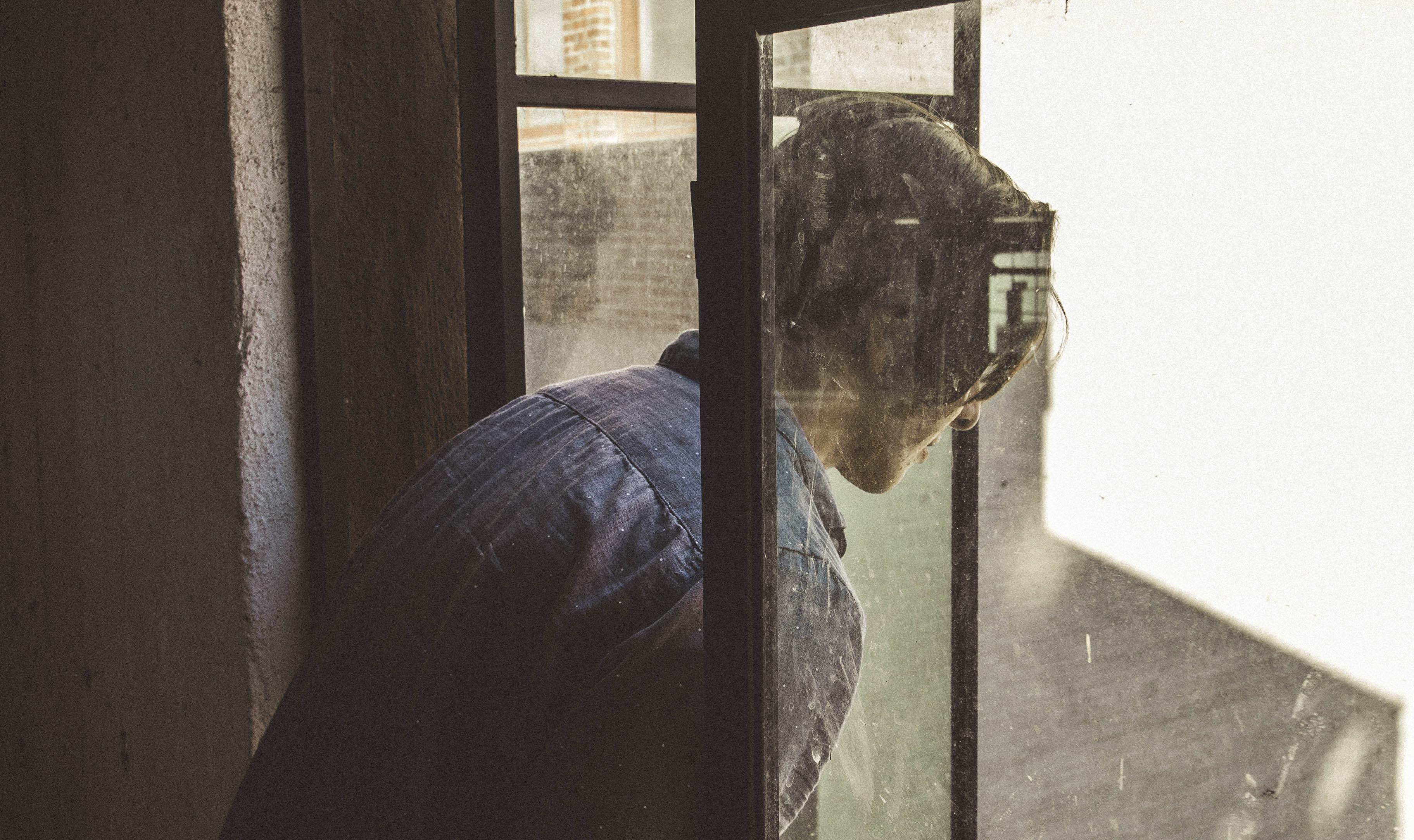 man staring on window