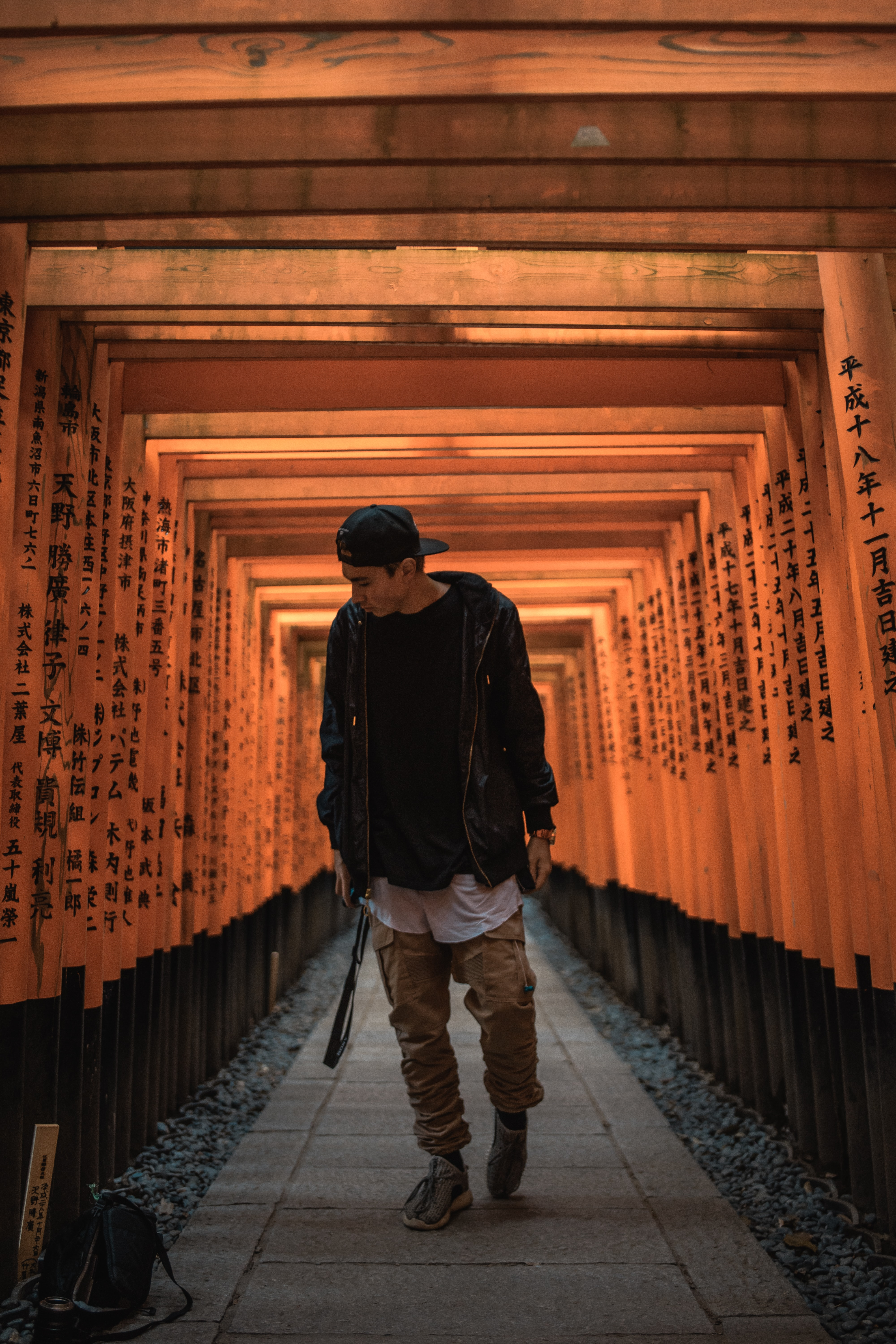 man standing between torii gate