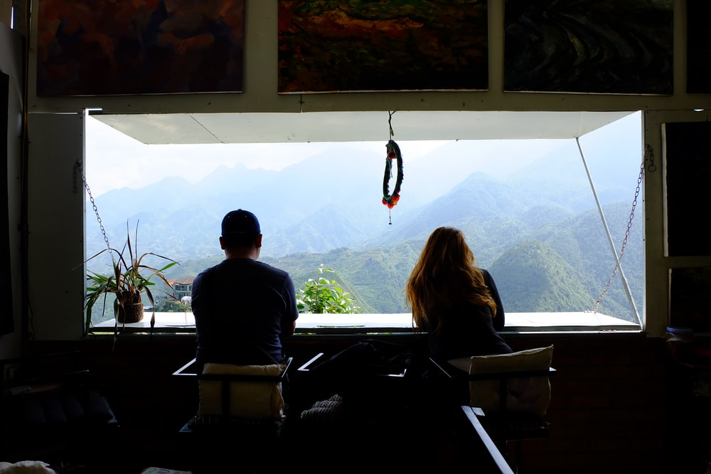 man and woman inside room in front of window seeing mountains