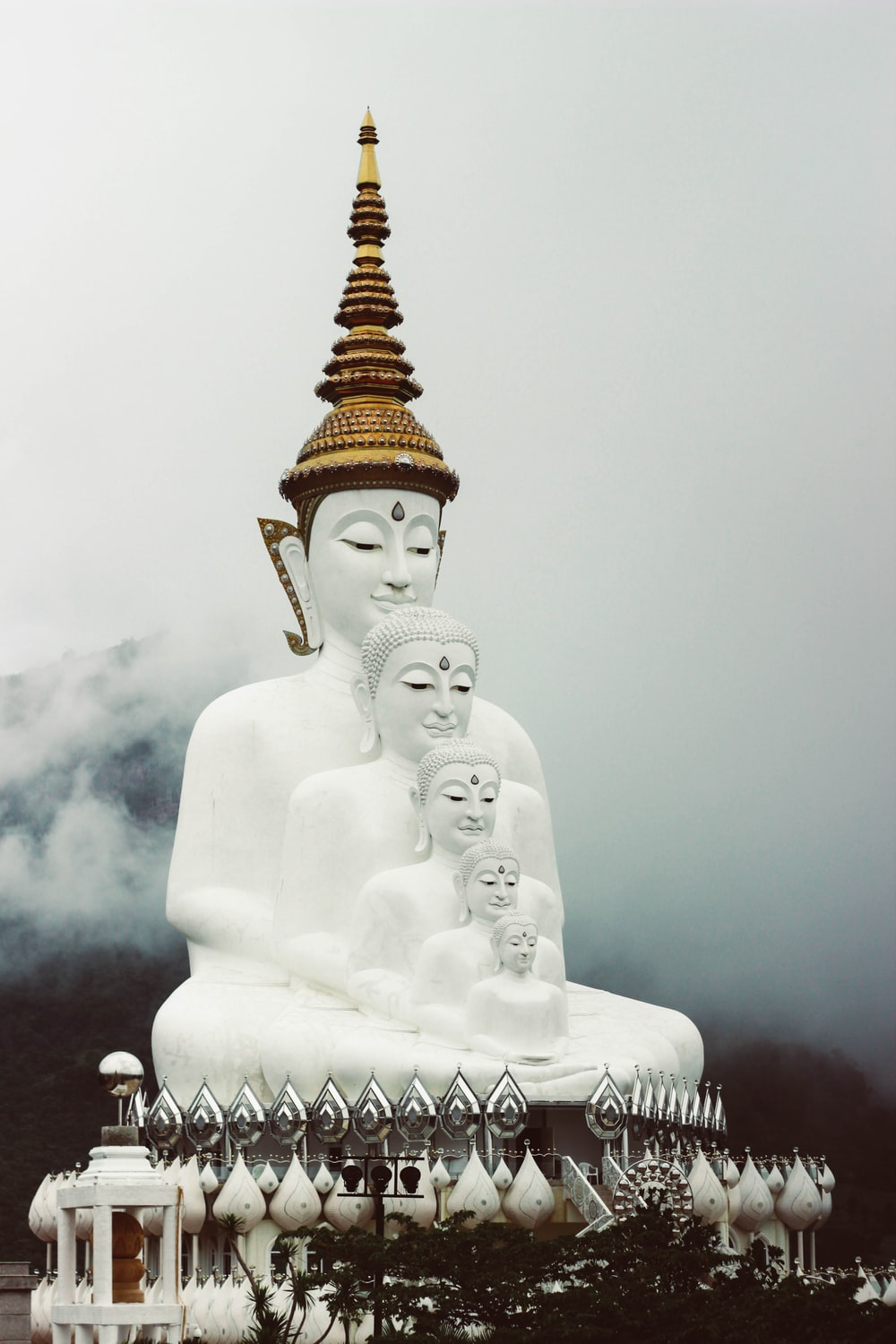 several white buddha monument overlooking hill covered on fog at daytime