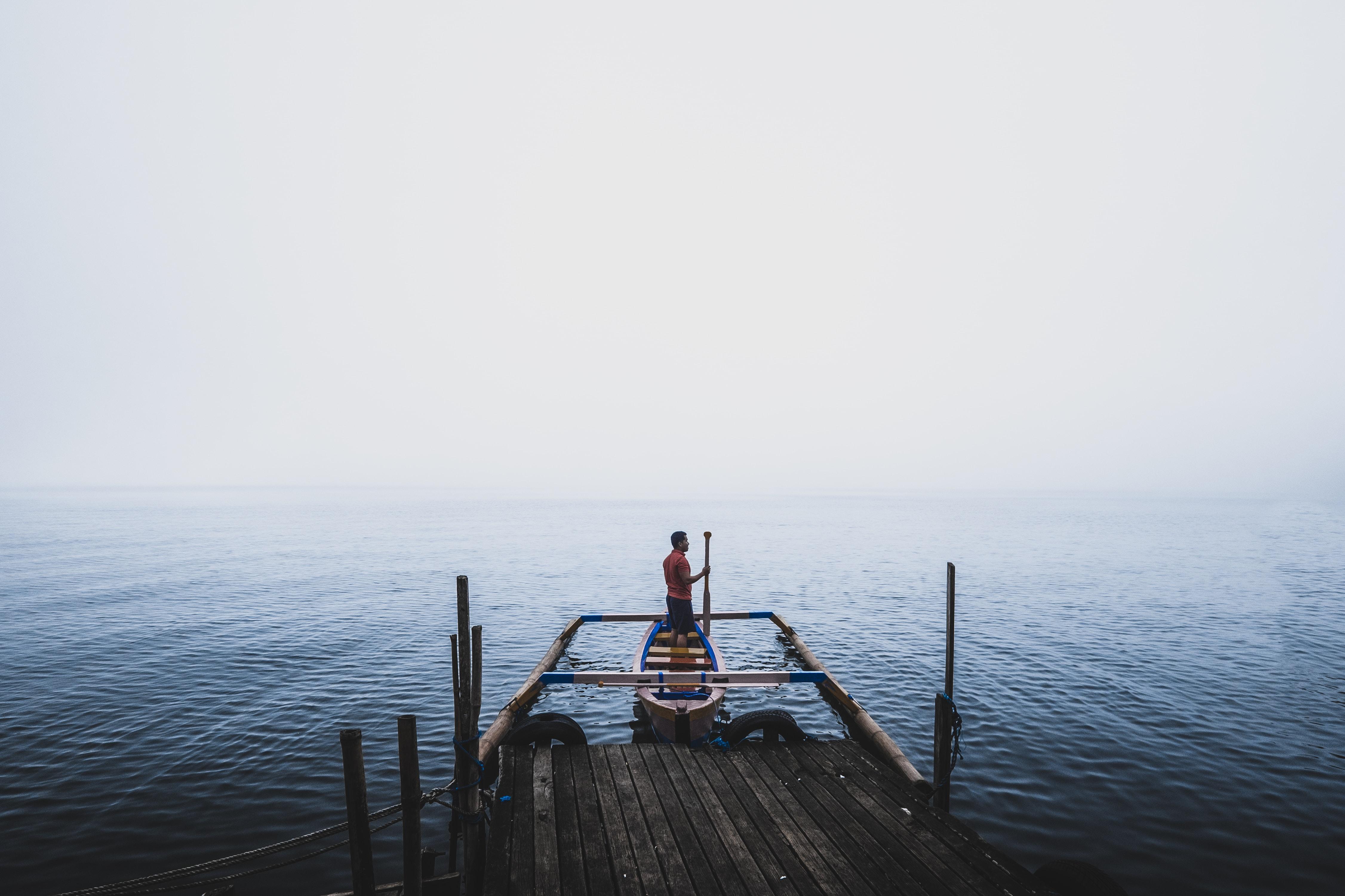man standing on canoe near dock during daytime