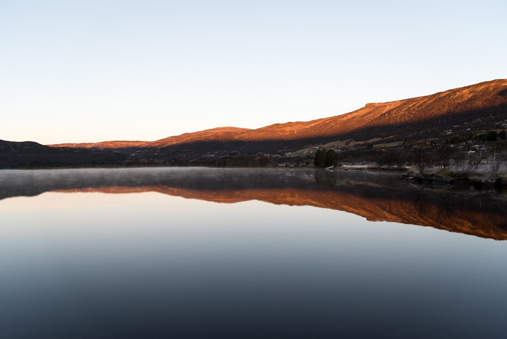 landscape photography of lake by the mountain under blue calm sky