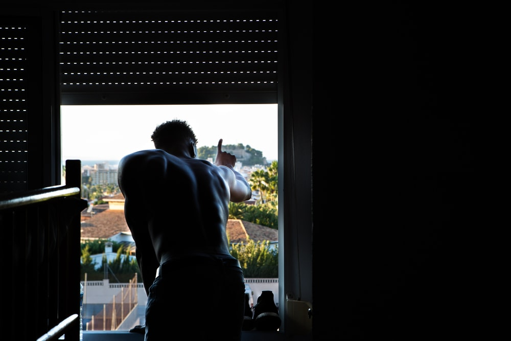 man leaning to window during daytime