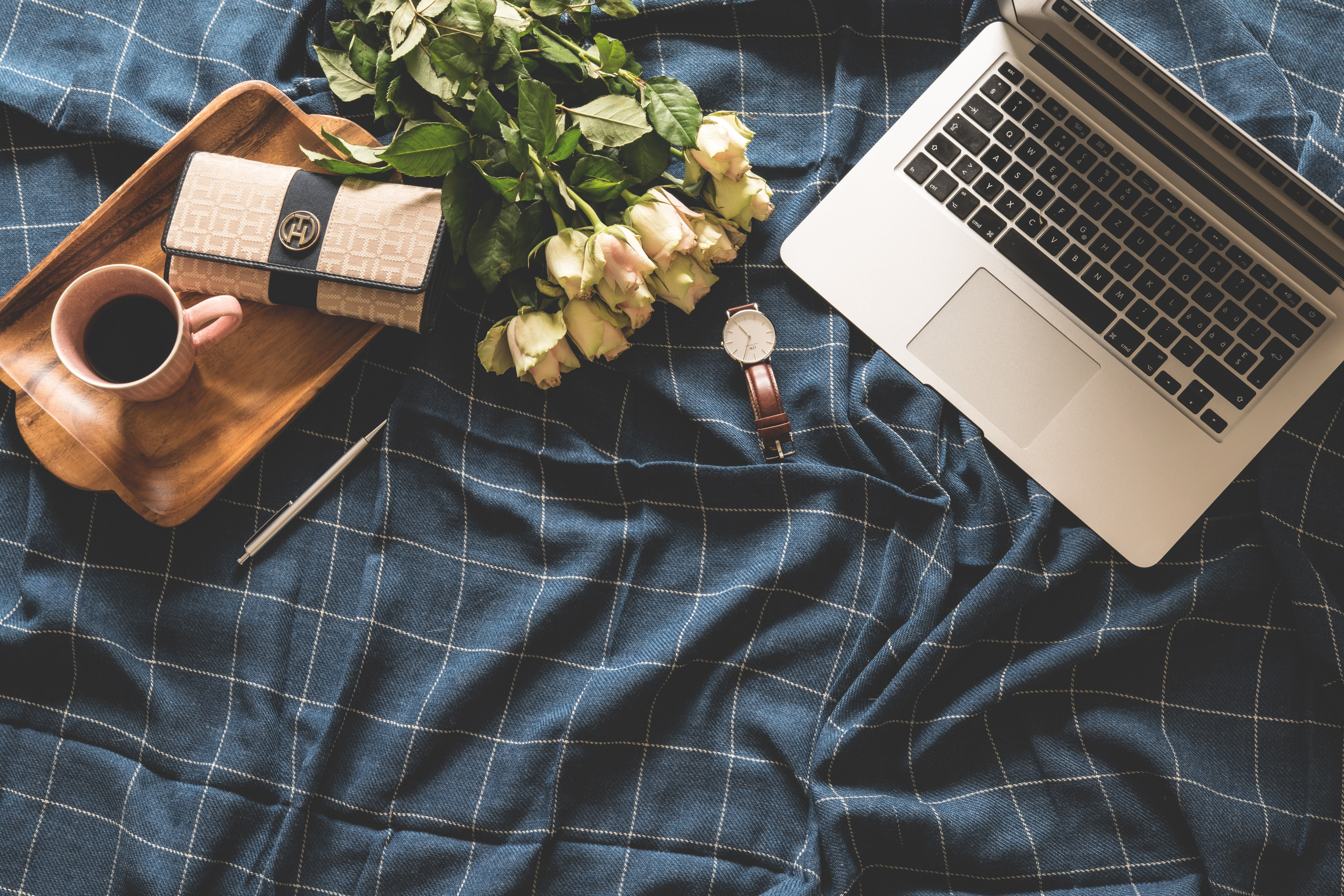 flat lay photography of MacBook Pro, wallet, watch, coffee, tray, and bouquet of flower