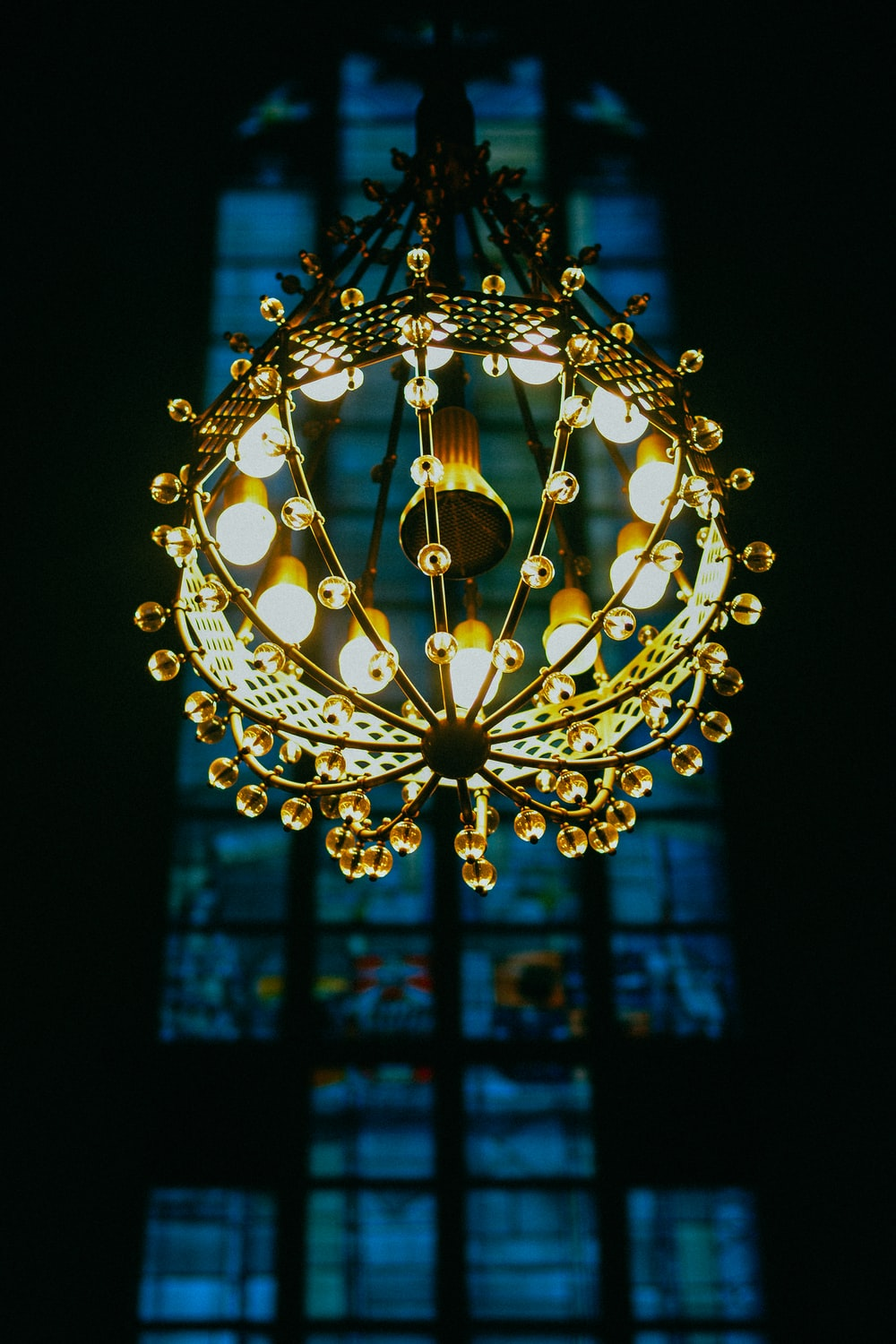 yellow lighted chandelier with stained glass window background
