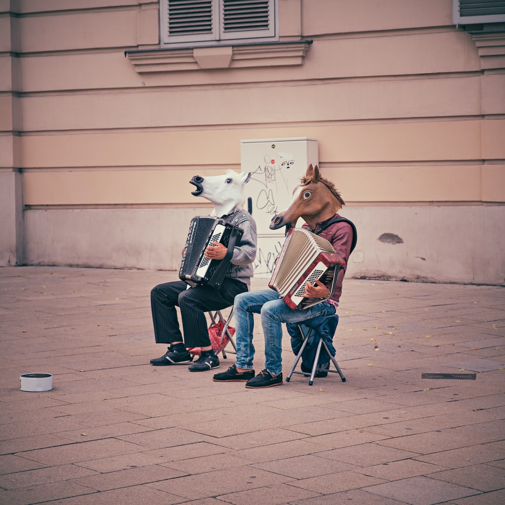 two person wearing horse heads sitting on folding chairs while playing accordions beside brown concrete building