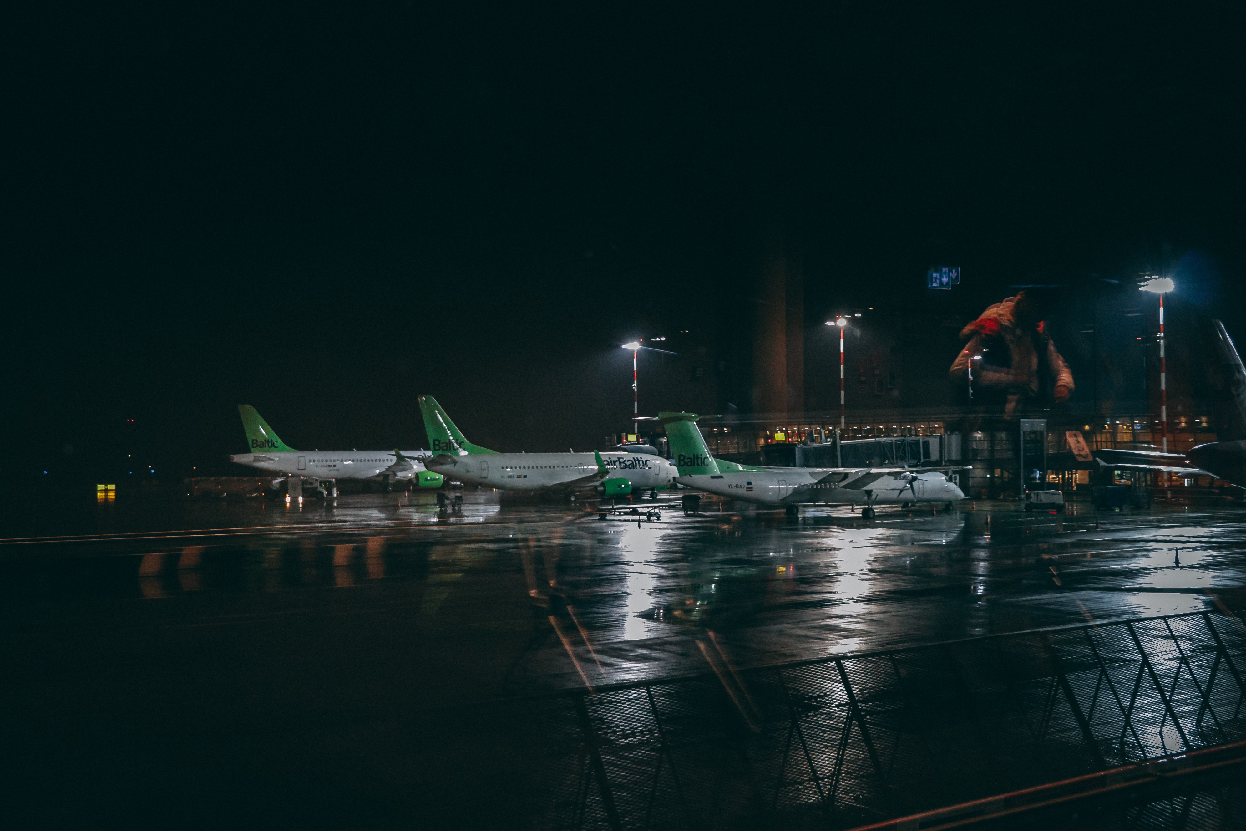 three white and green plane on the airport photography during nighttime
