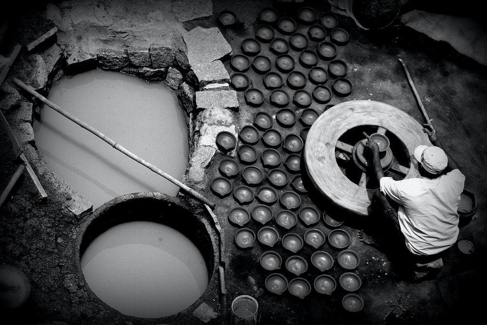 greyscale photography of man making clay bowls