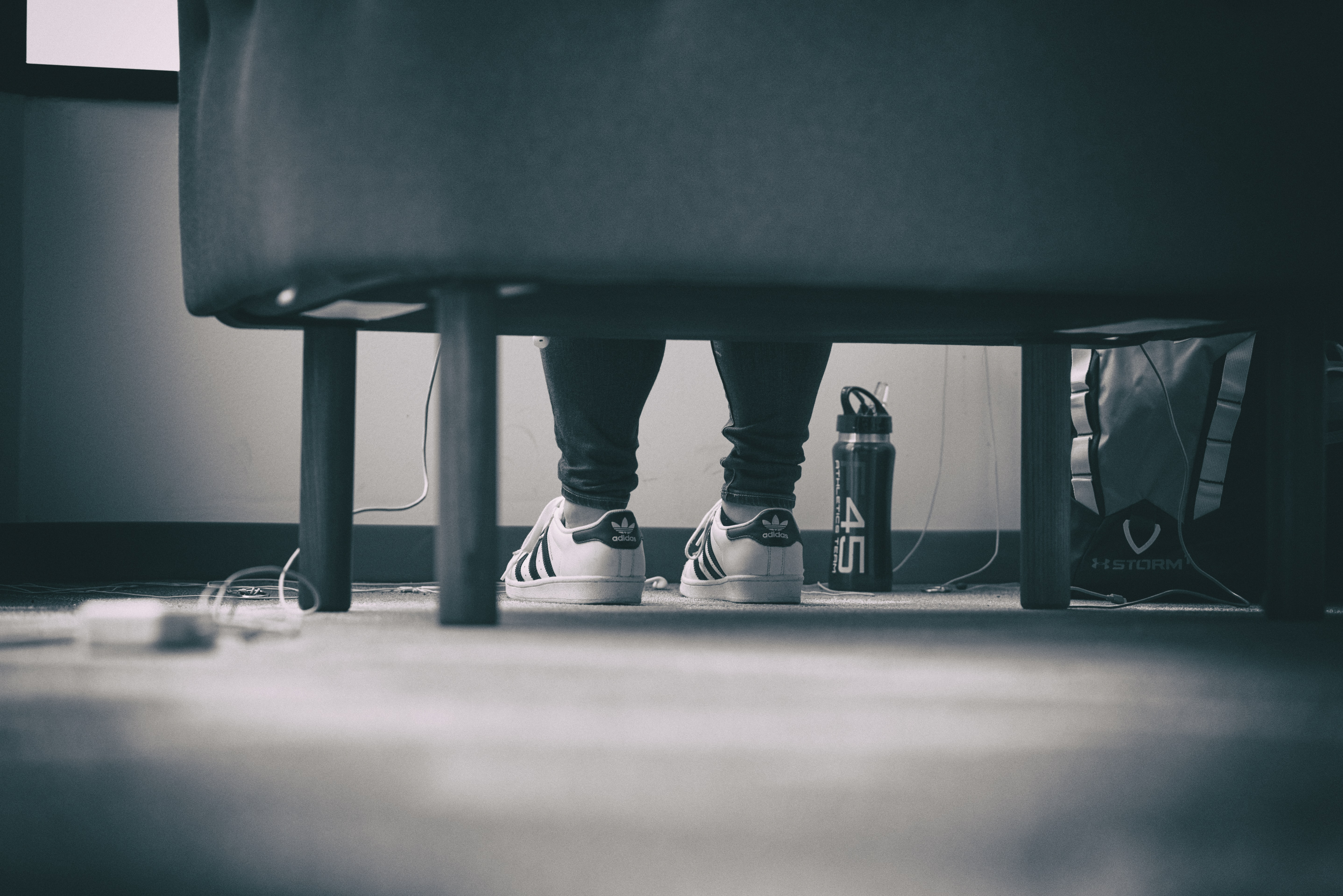 grayscale photo of person wearing adidas Superstar sitting down