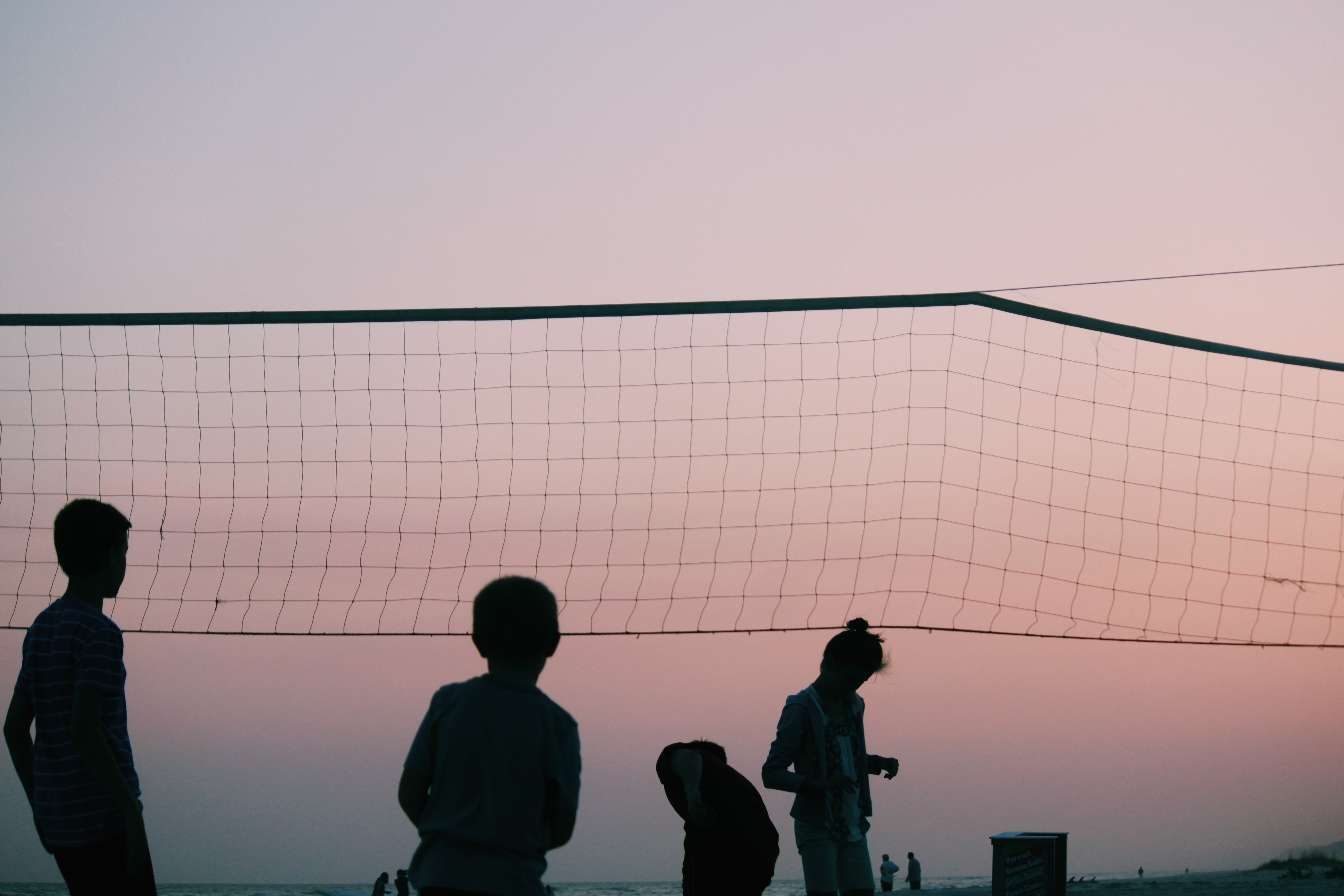 silhouette of four people playing volleyball during nighttime