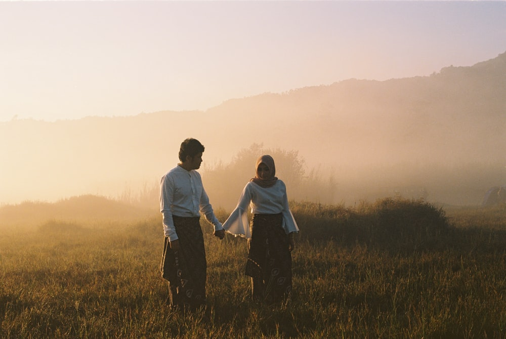 couple standing on grass field with fogs