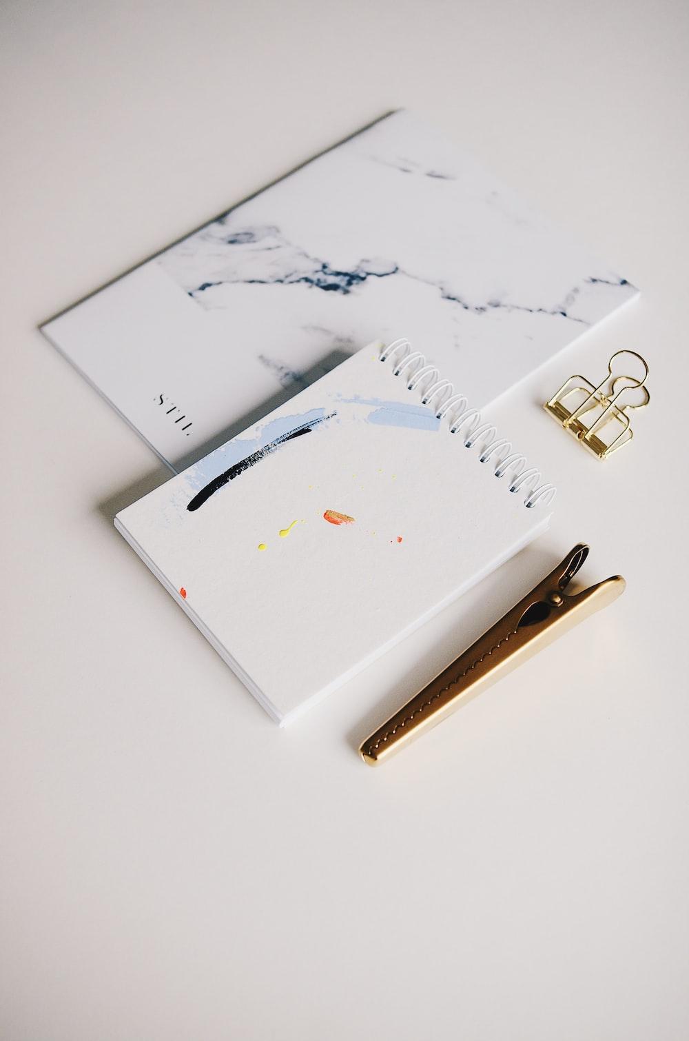 white spiral notebook beside brown clip
