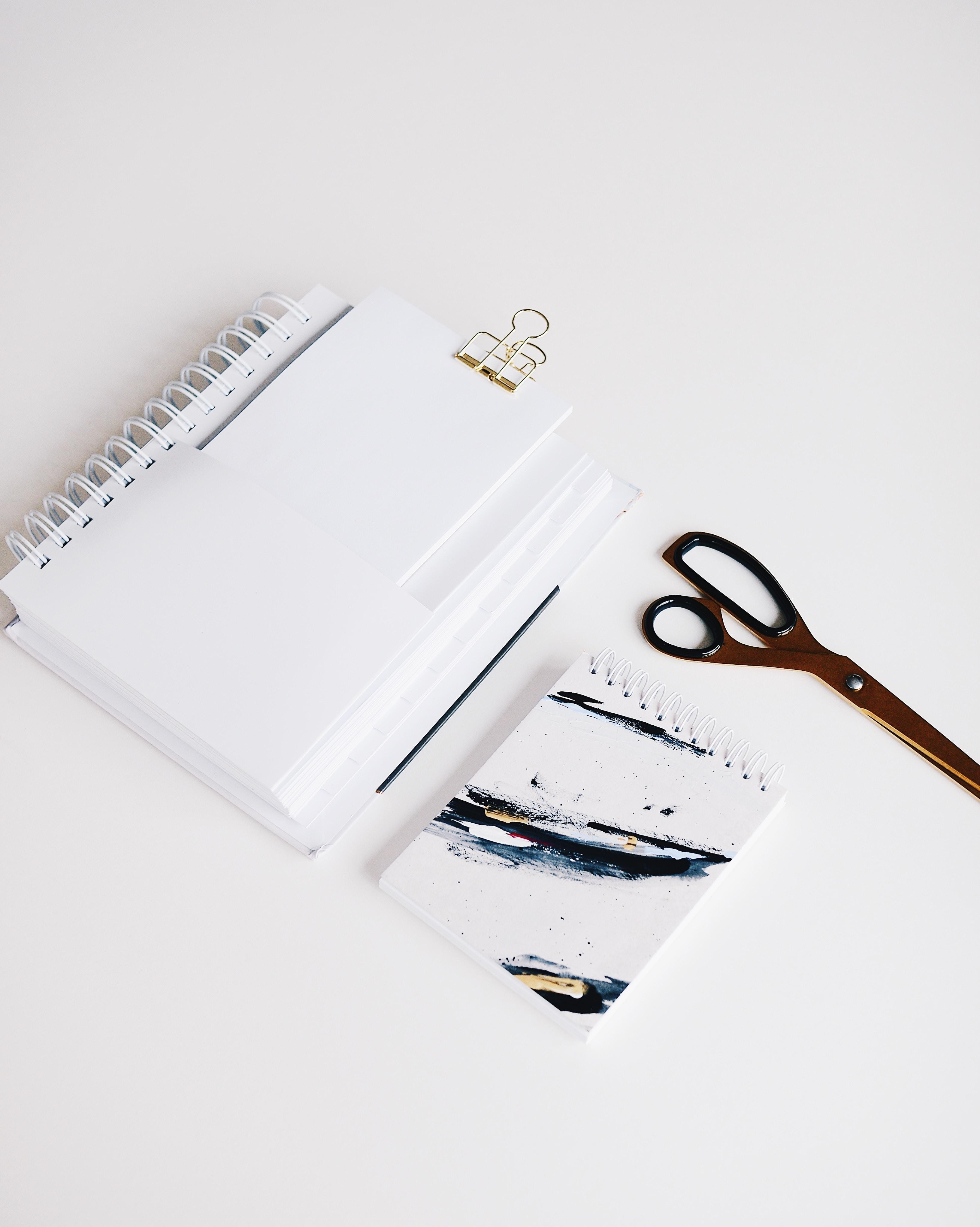 brown scissors near notebooks