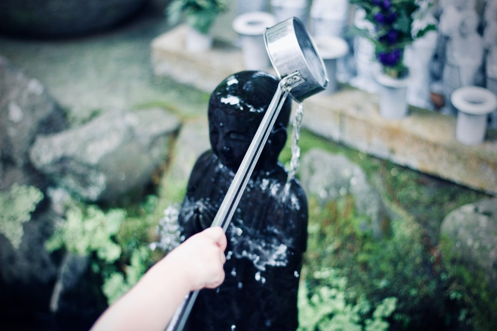 person watering figurine during daytime