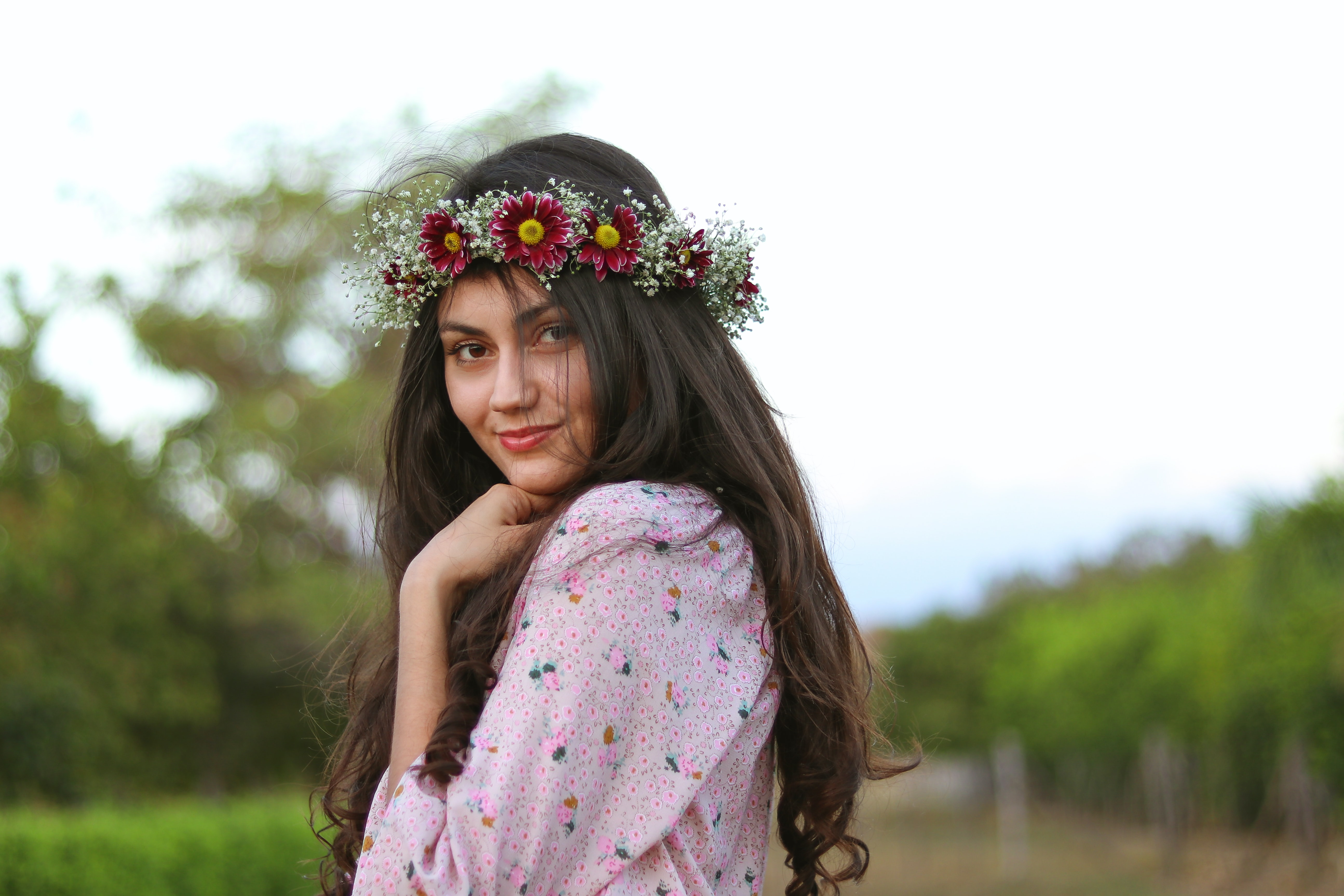 woman with floral headdress holding her chin