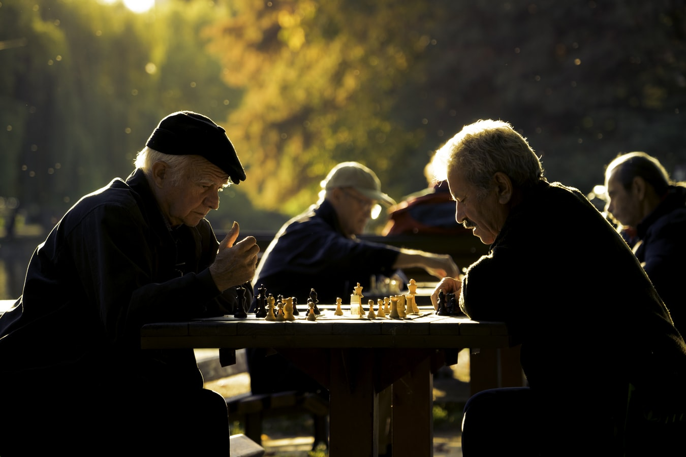 Two elderly men playing chess in a park.