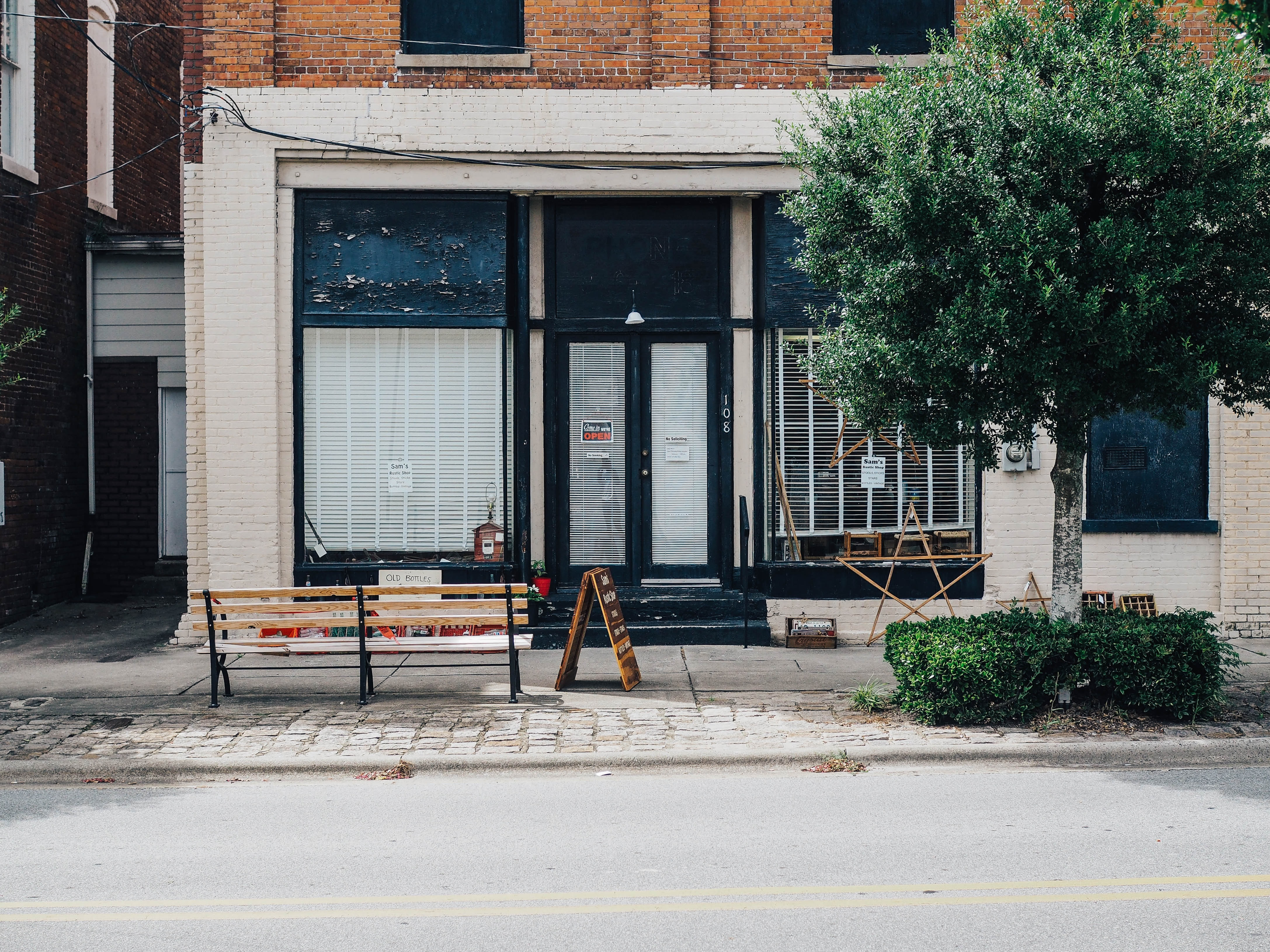 brown wooden bench in front of black store