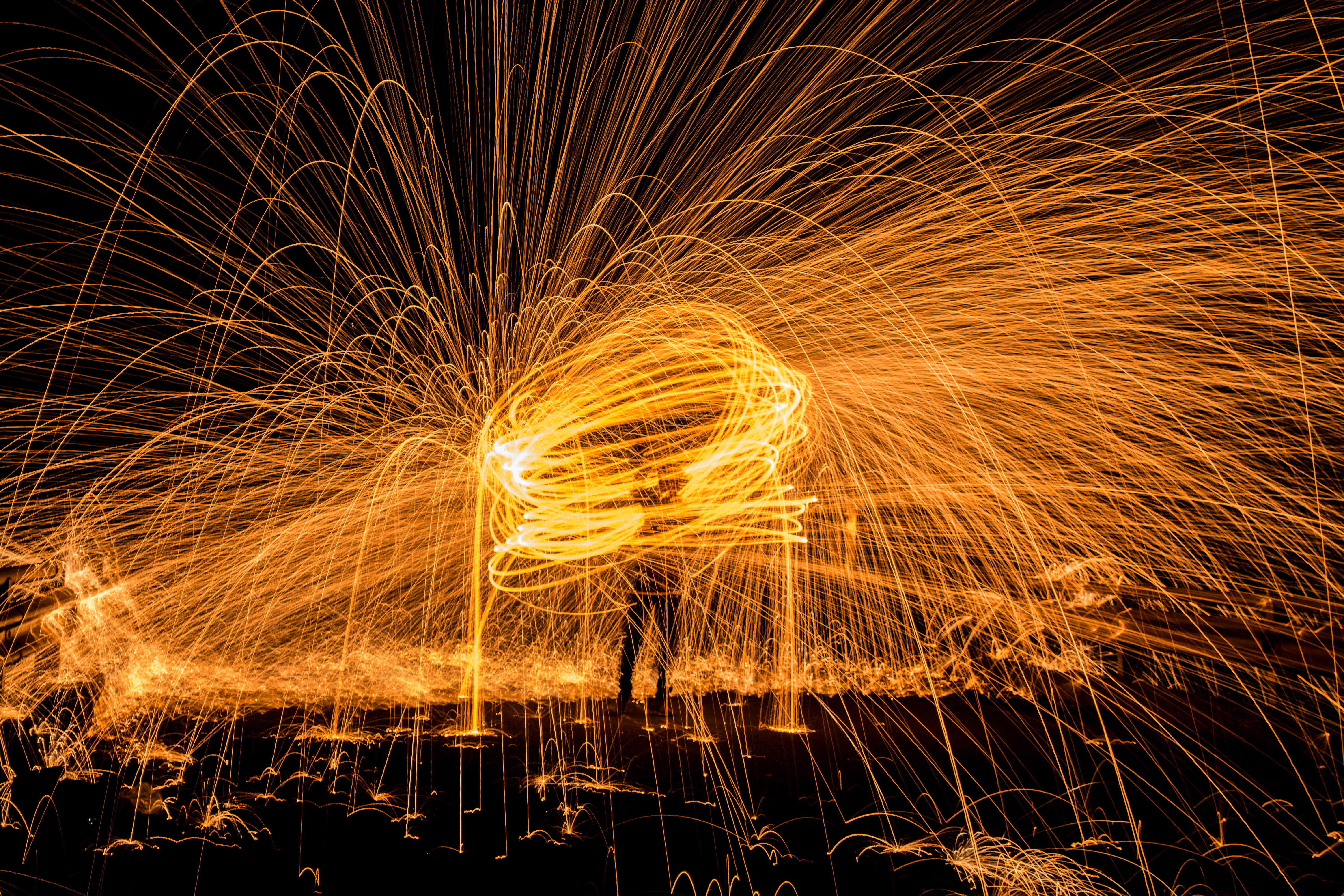 steel wool photography on man standing on black surface