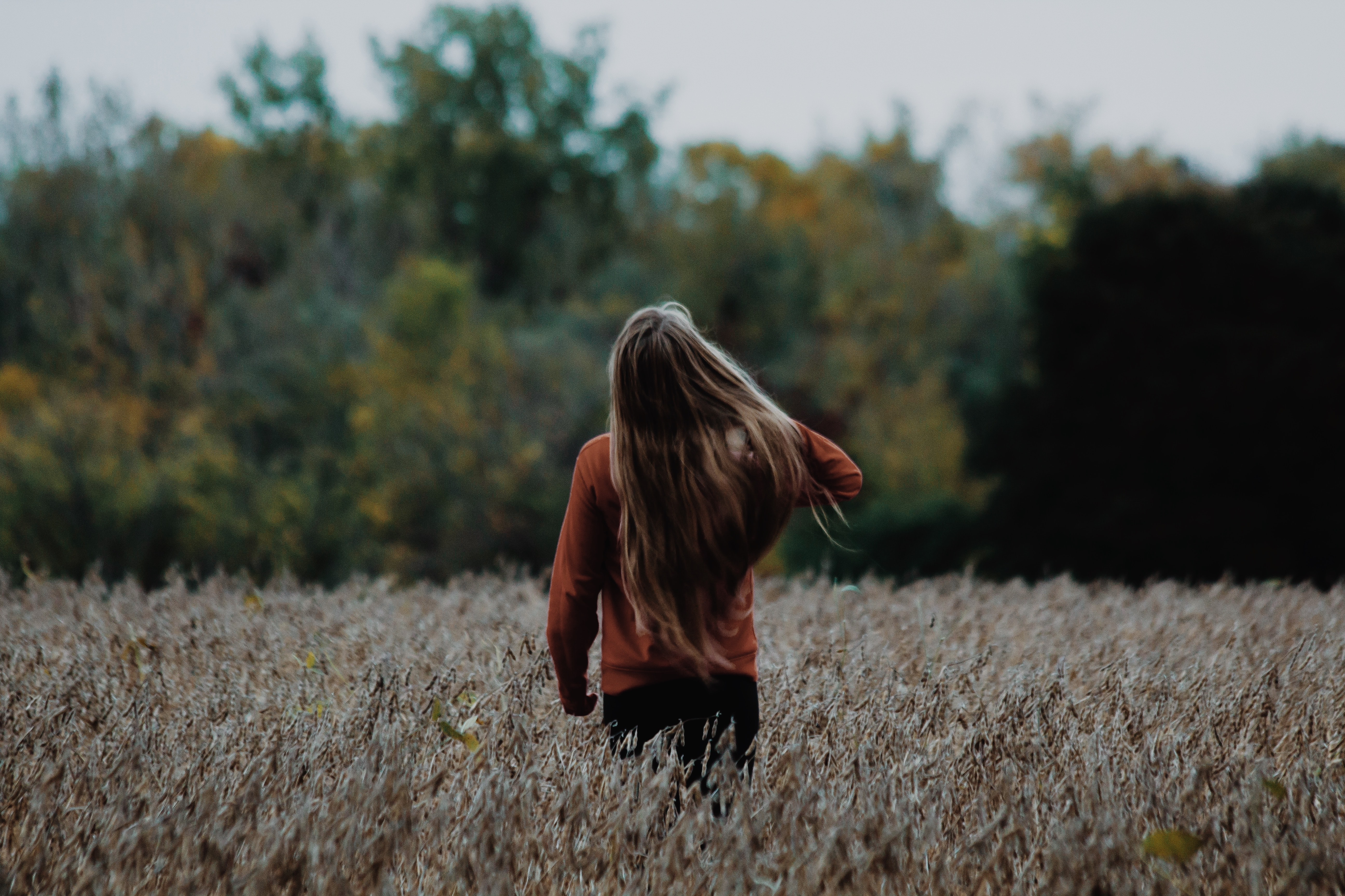 woman holding her hair standing at grass field