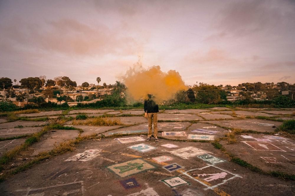 man standing surrounded by yellow smoke taken at daytime