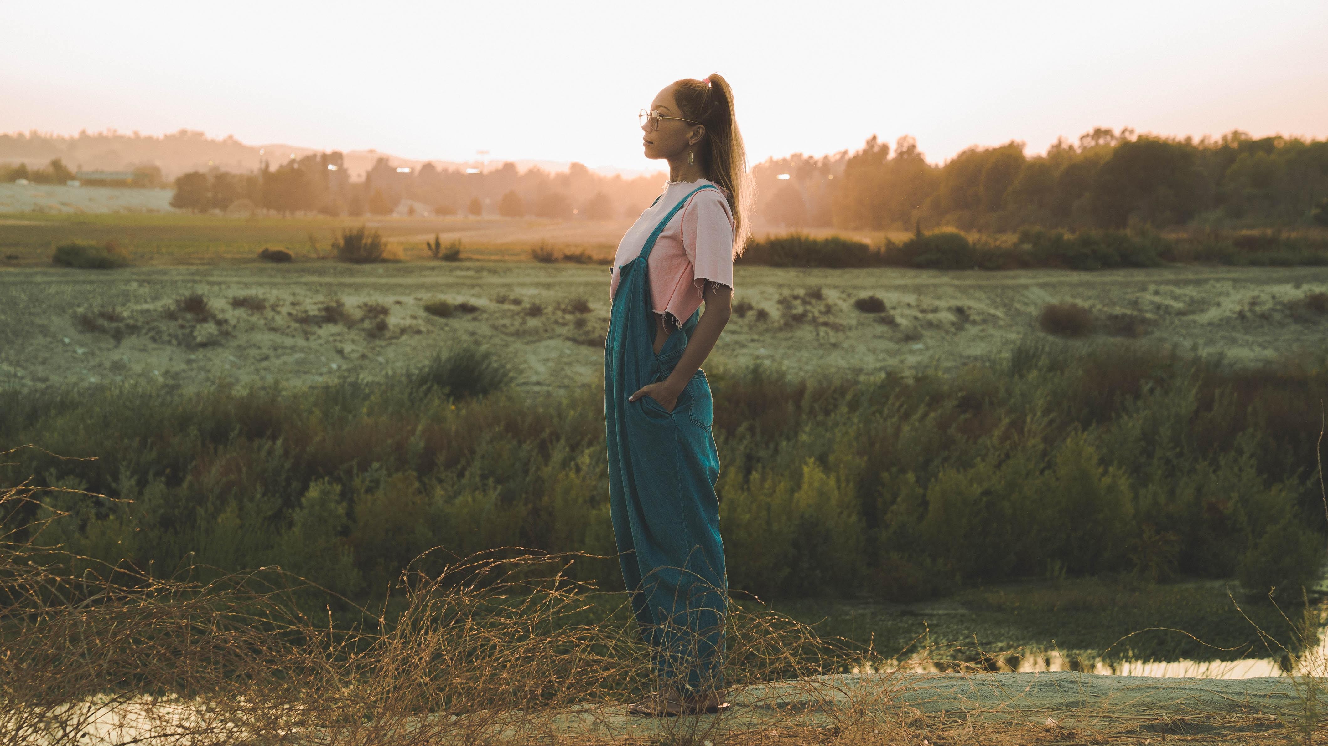 woman in green jumper standing near grass field