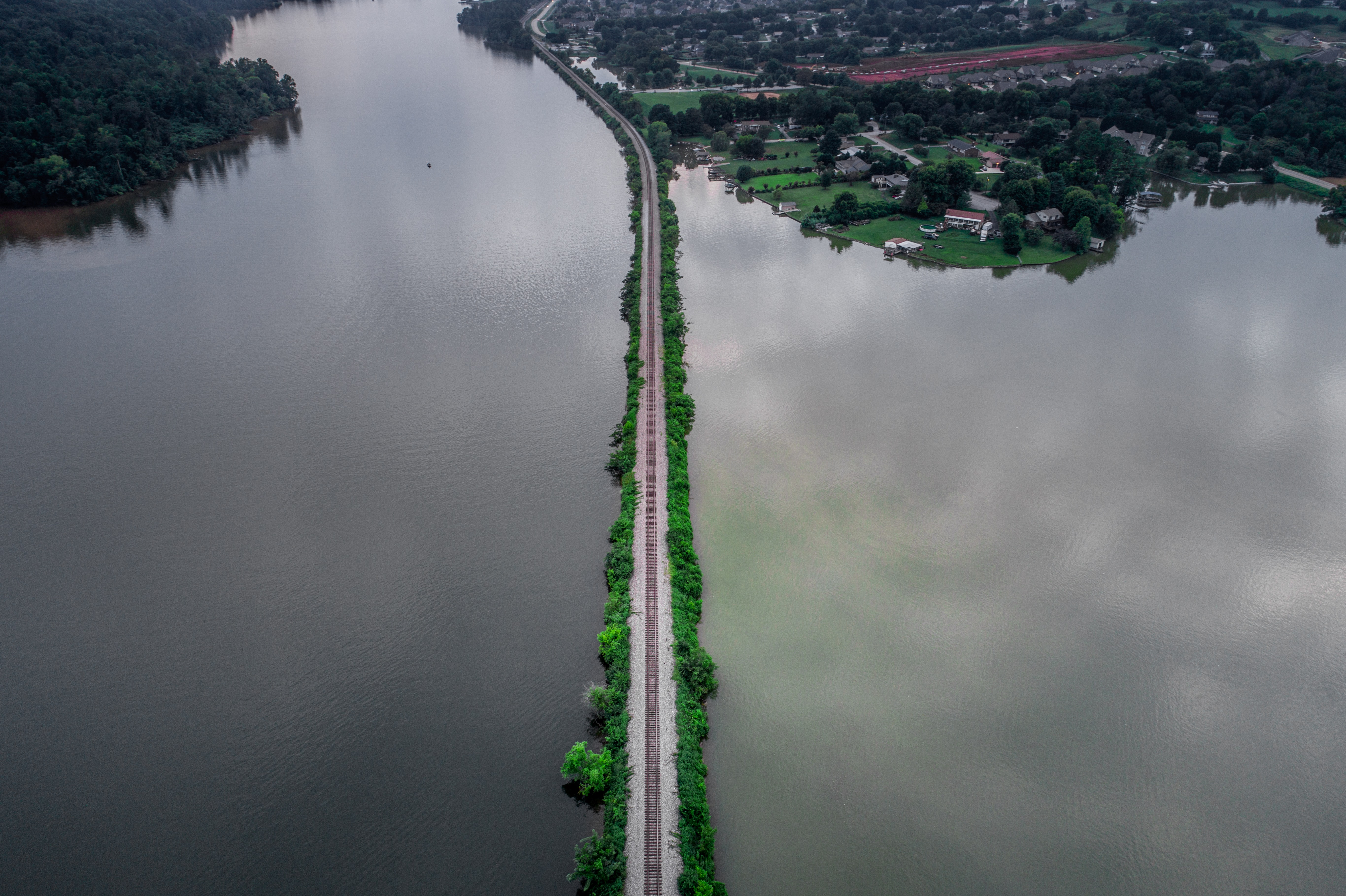 road between body of water during day