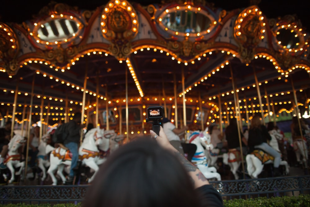 people riding merry go around at the carnival during night