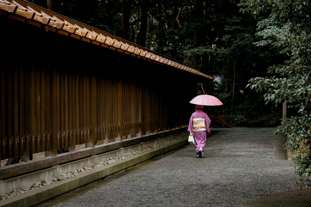 geisha holding umbrella near fence