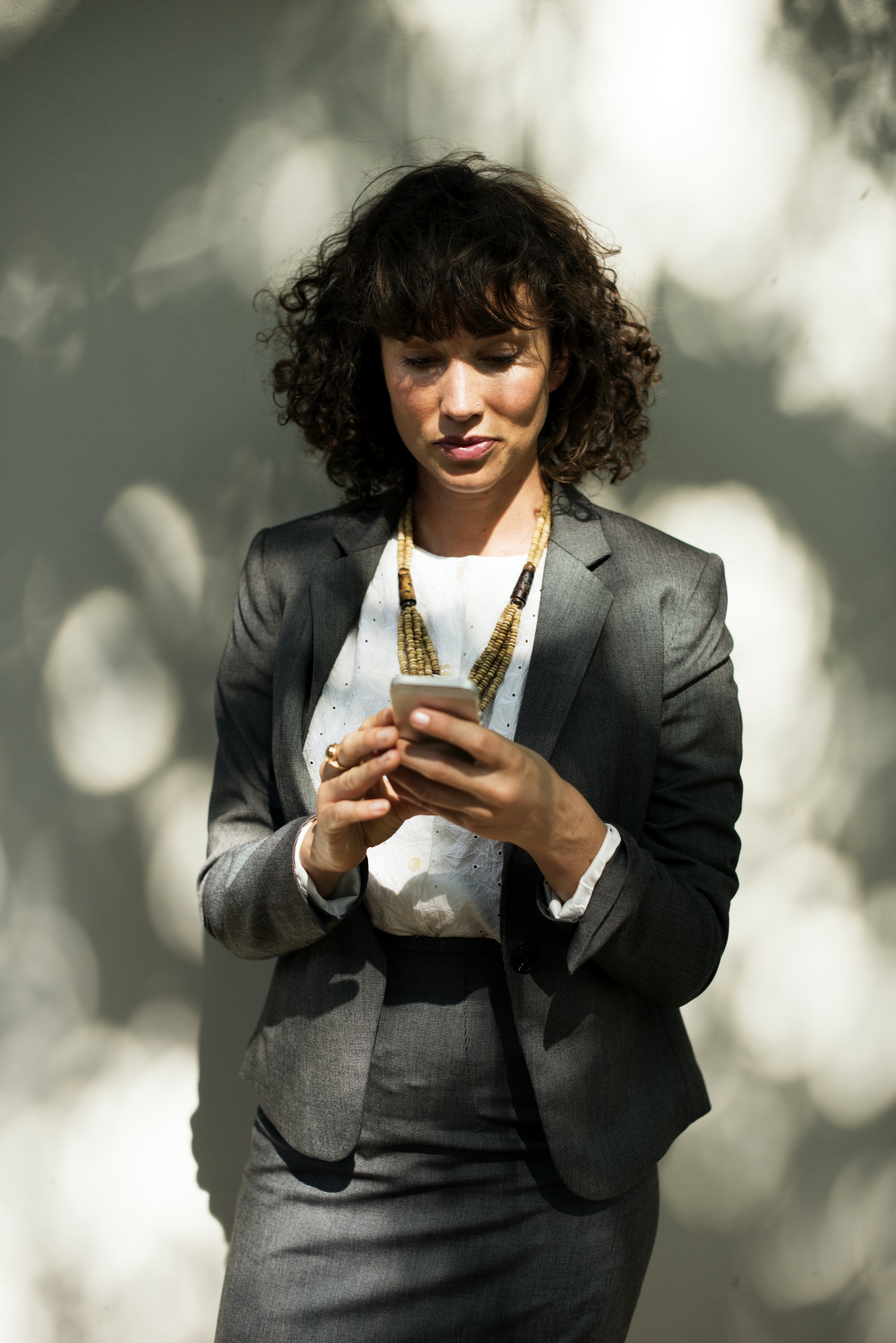 woman in black suit holding smartphone behind wall