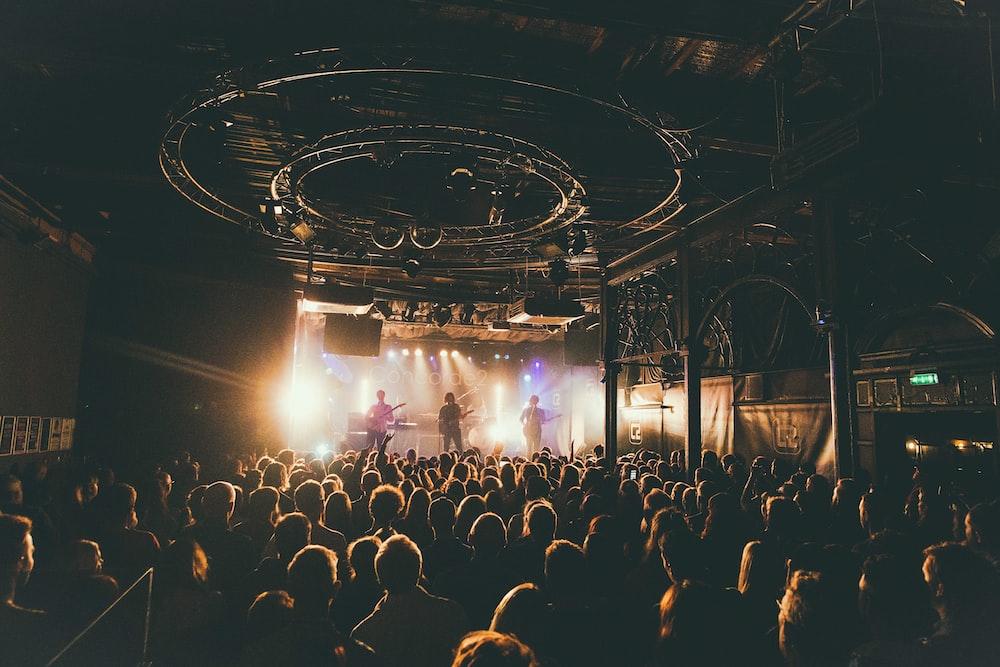 people attending concert inside dark room