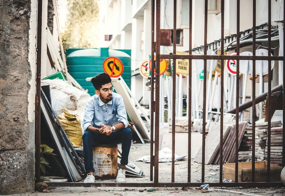 man sitting beside gate