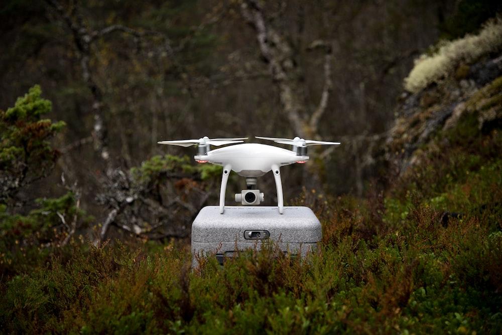 white and gray DJI Phantom drone on gray box