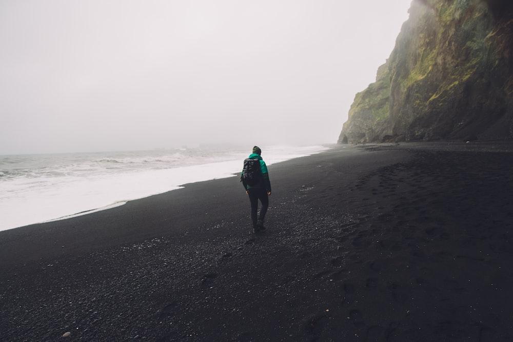 man walking on black seashore