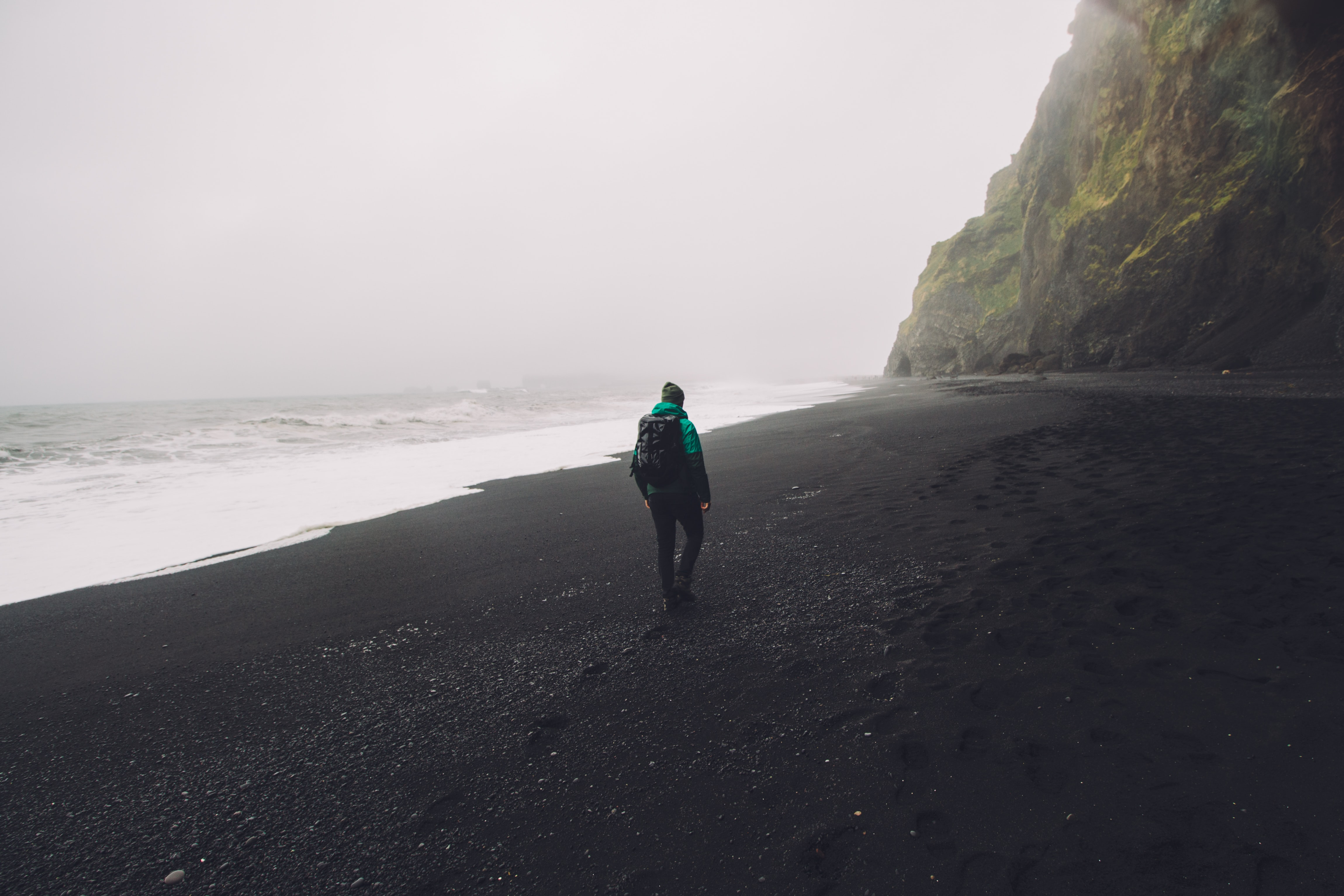 man walking on black seashore