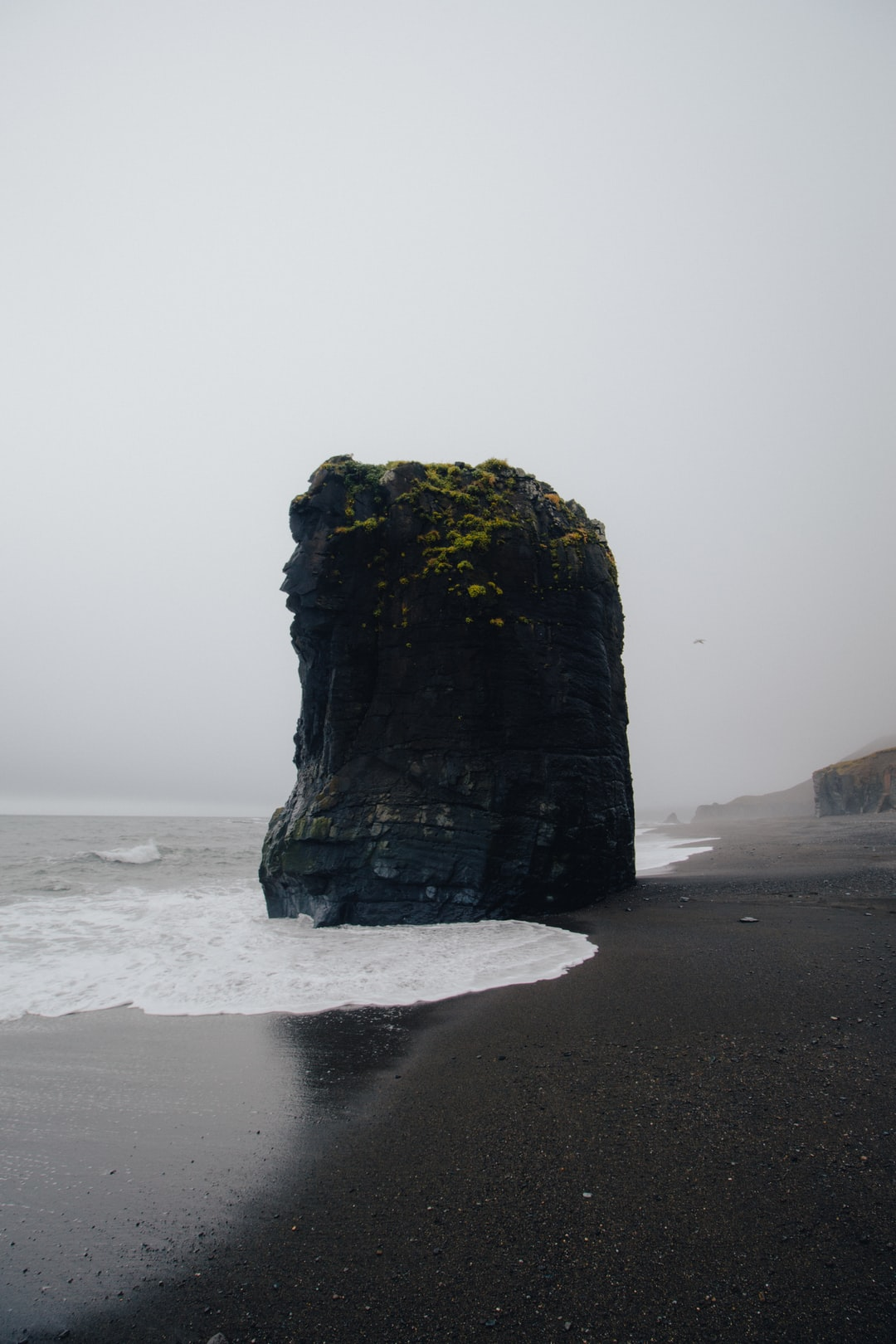 A stubborn rock stands tall in the middle of a black sand beach in Iceland.