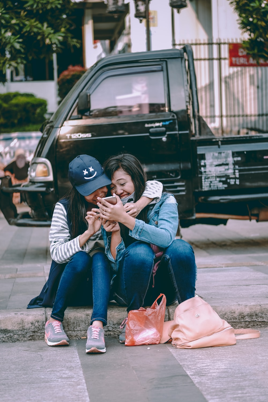 woman sitting on gray concrete street gather