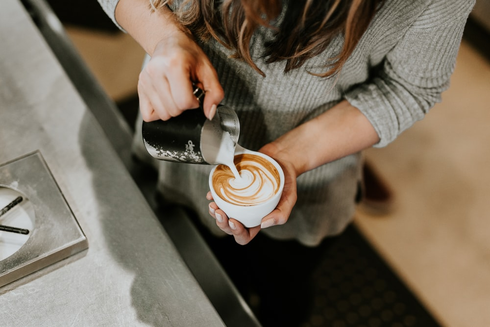 person pouring cup of coffee in white ceramic cup