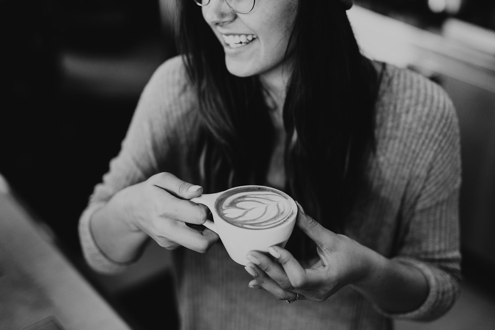 grayscale photo of woman holding coffee