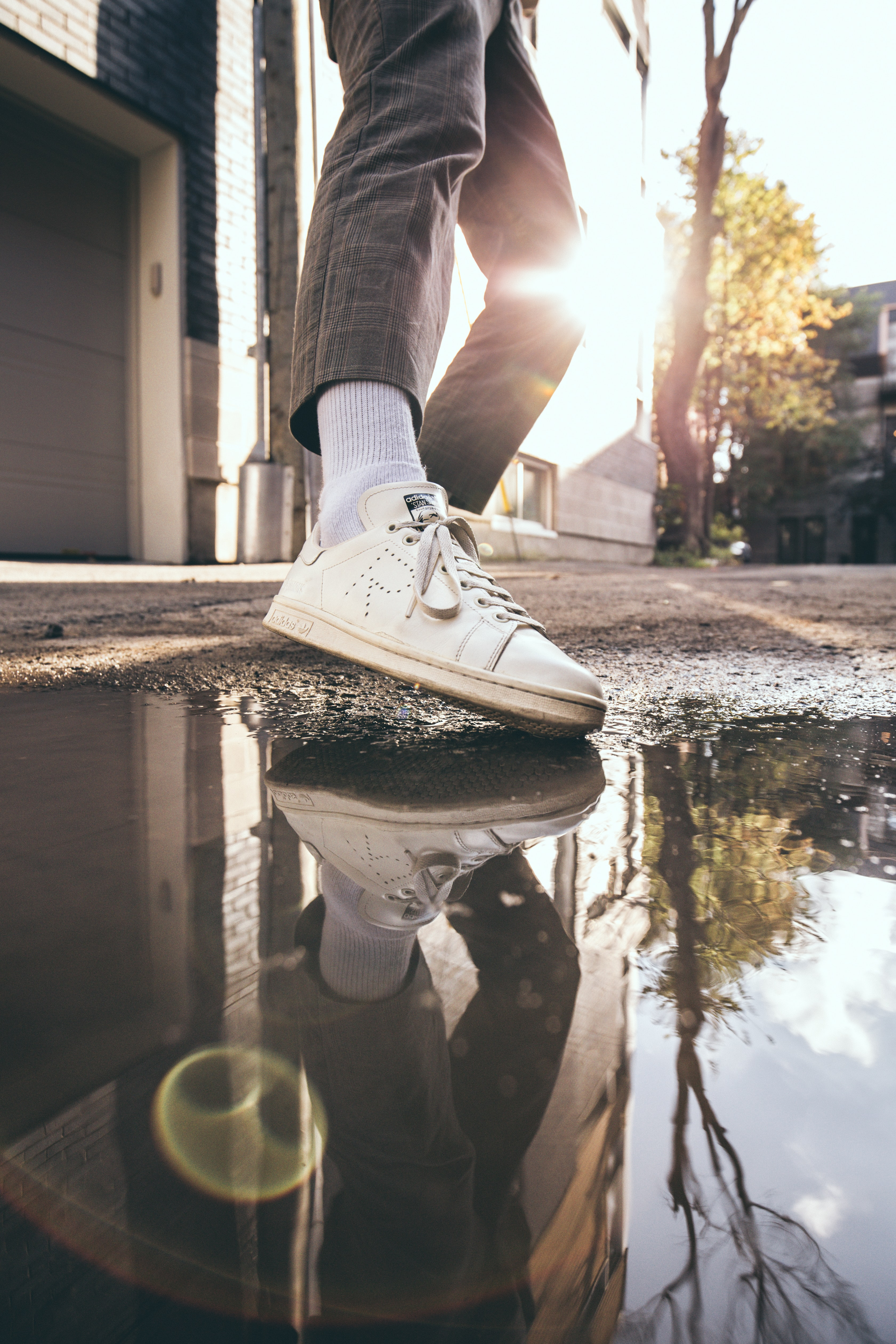 person in black pants and white shoe during daytime