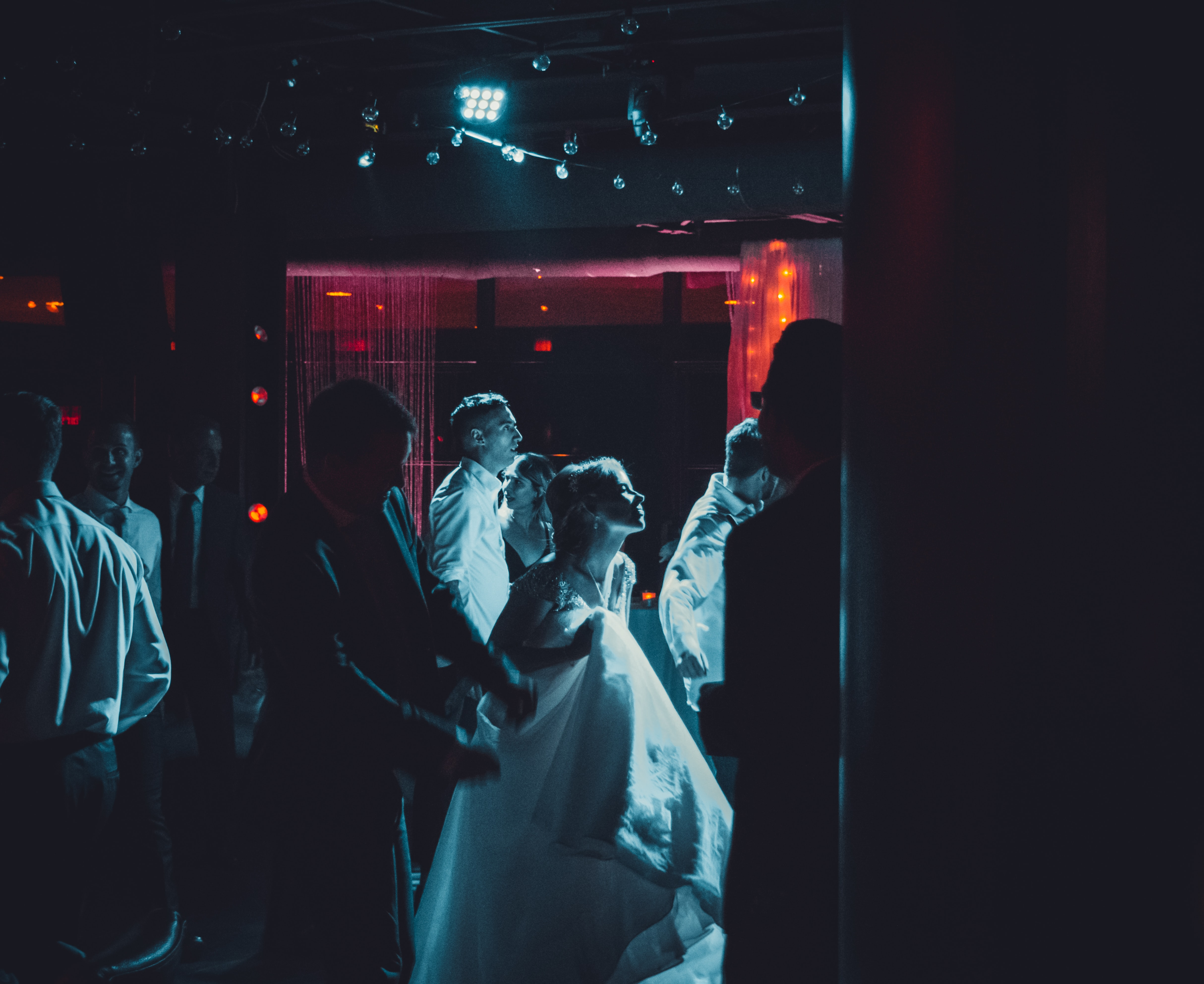 woman wearing white dress surrounded by people inside building